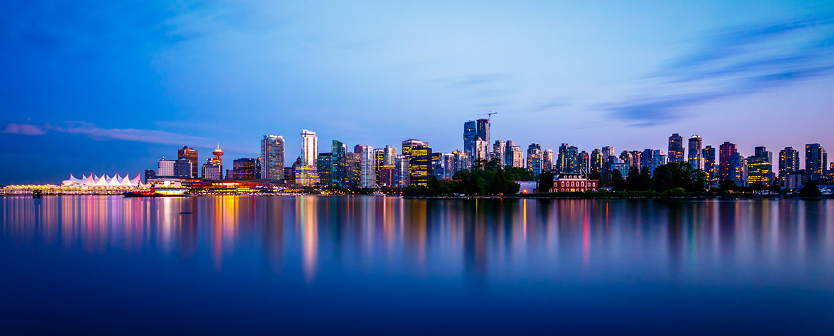 The lights of the Vancouver skyline light up the early morning twilight and the water.