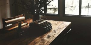 Typewriter on a beautiful wood desk by the window